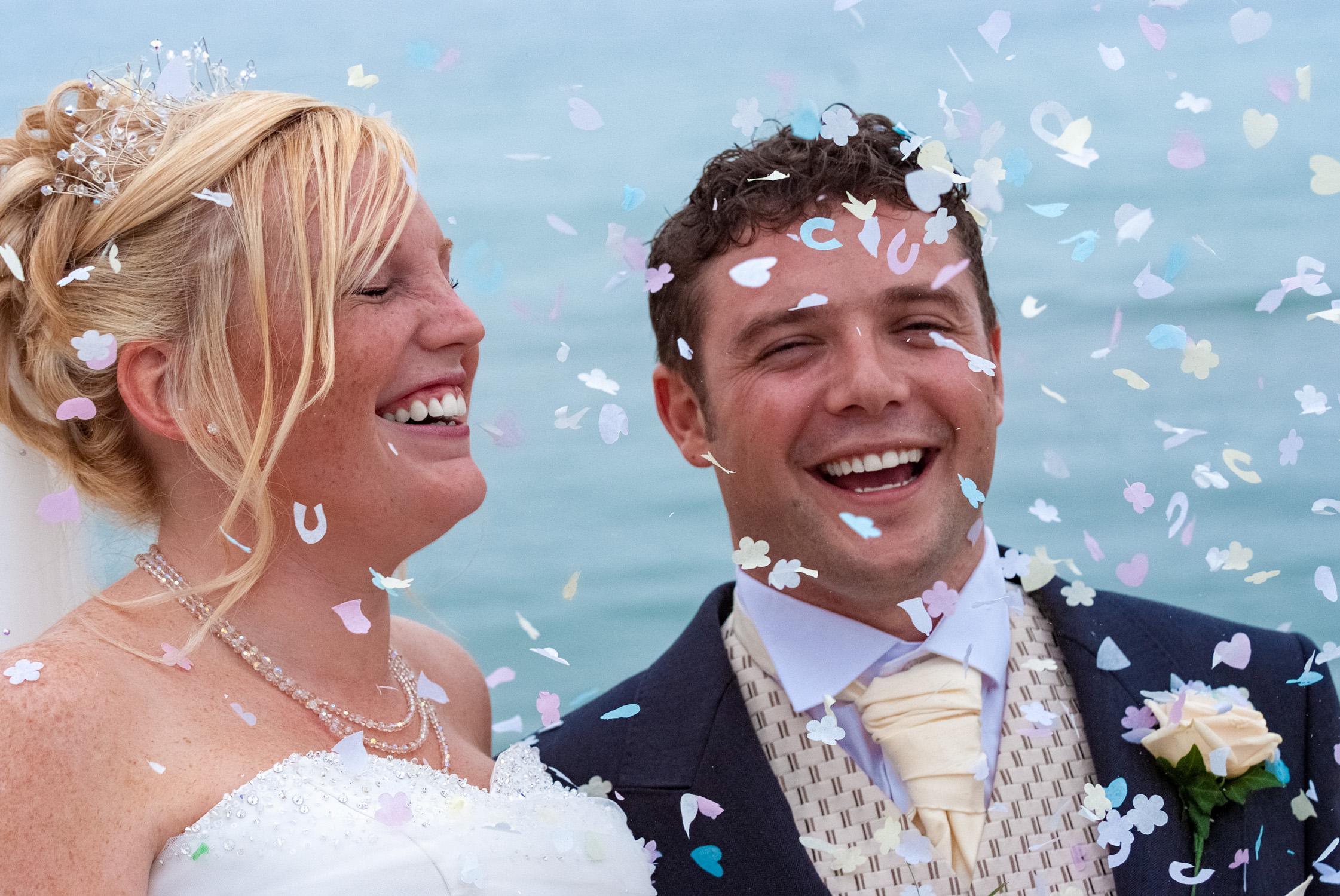 bride and groom laughing on a beach