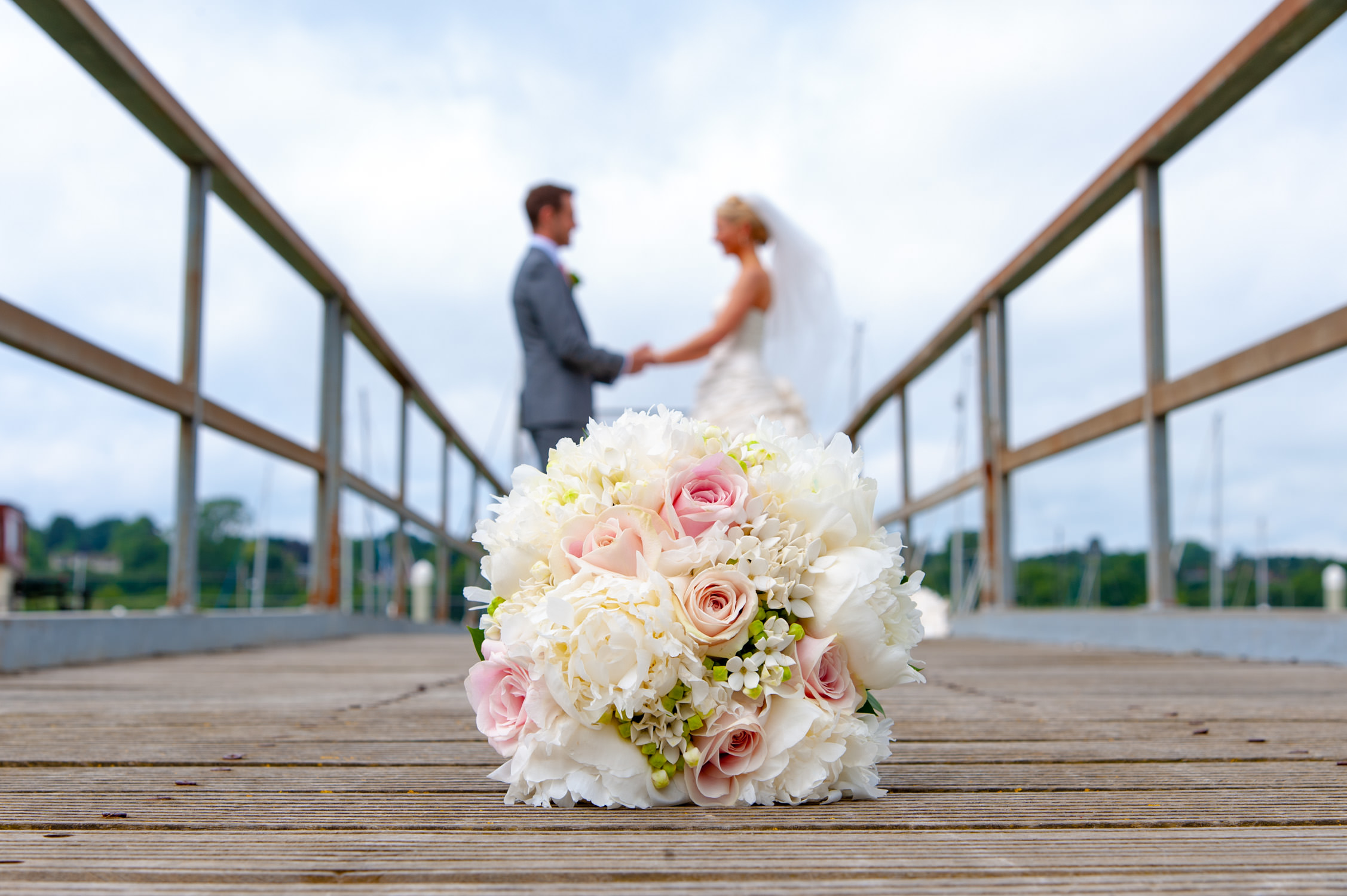 wedding bouquet in front of bride and groom