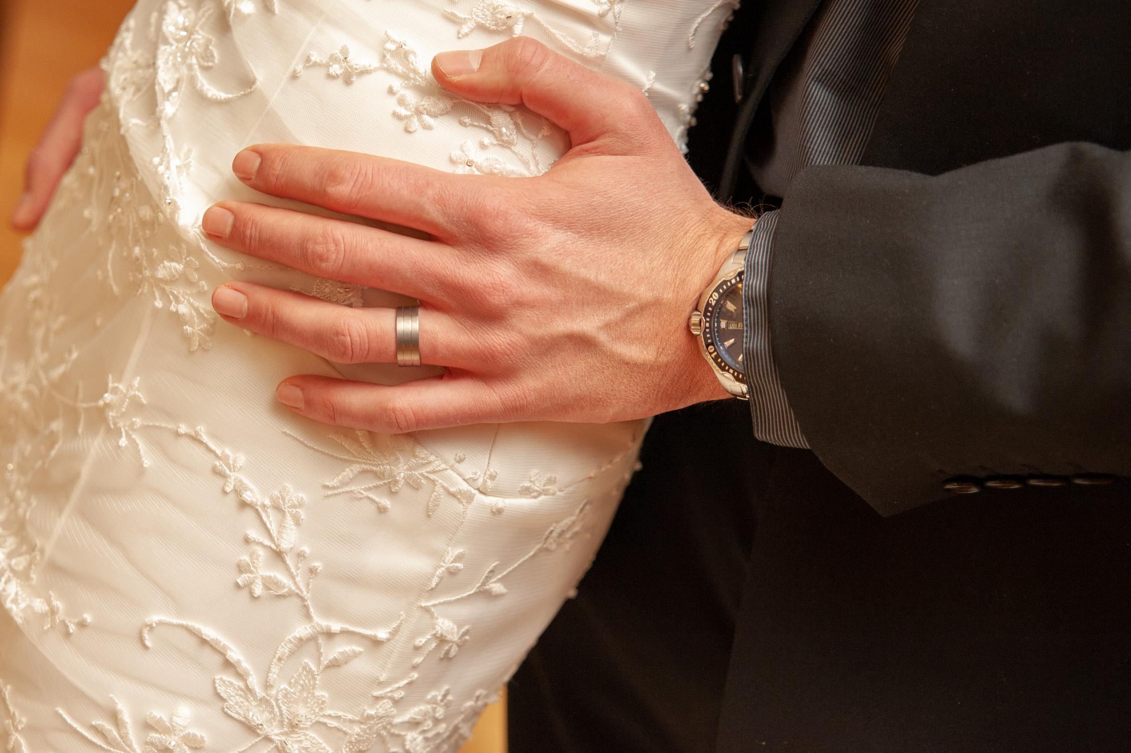 grooms hand on brides waist
